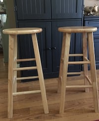 two round beige wooden bar stools