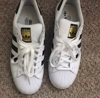 Pair of white adidas superstar shoes