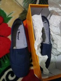pair of black slip-on shoes with box