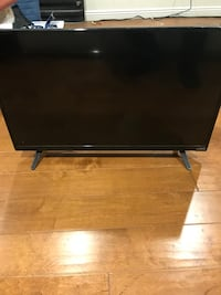 black flat screen TV with remote Los Angeles, 90019