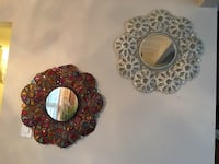 Two round floral framed wall mirrors
