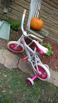 white and pink bicycle with training wheels