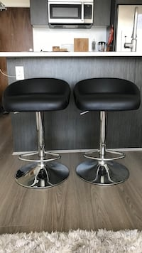 Two stainless steel base black leather padded bar stools
