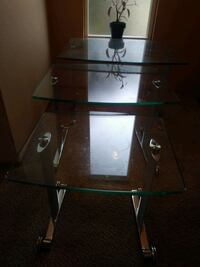 Glass end tables, three range in size from small to large.