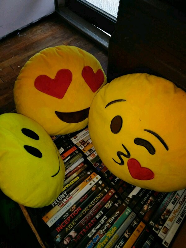 two yellow and red emoji plush toys
