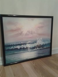 painting of body of water with black frame