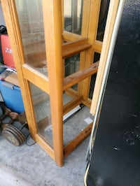 glass cabinet with 4 shelves and 4 glass doors with a light on top and