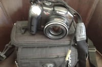 Black Canon DSLR camera with bag and two memory cards