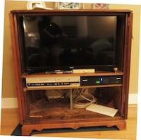 black flat screen TV with brown wooden TV stand Paterson