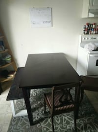 rectangular black wooden table with four chairs dining set Calgary, T2K 4A1