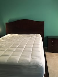 Quilted white mattress and brown wooden bed