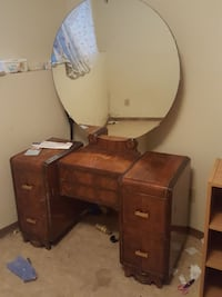 brown wooden vanity table with round mirror