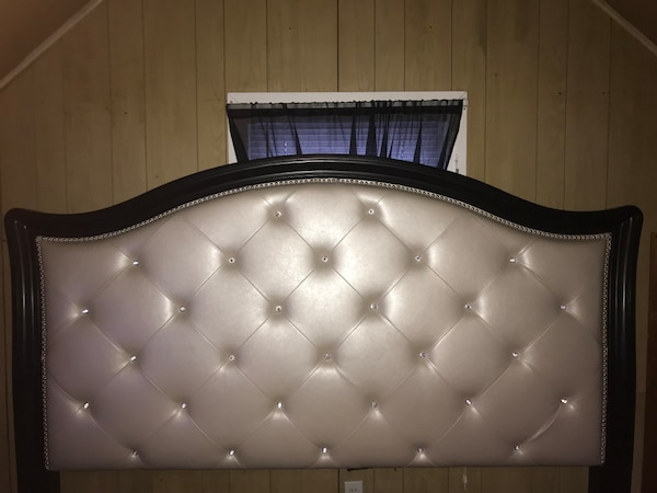 Tufted gray leather headboard with black wooden frame