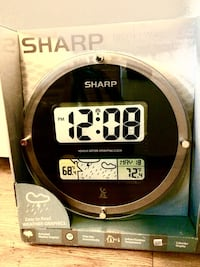 round black Sharp digital wall clock
