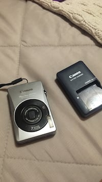 Gray Canon point-and-shoot camera with battery charger set