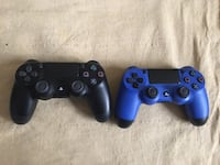 two blue and black Sony PS4 controllers