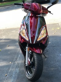 red and black Honda motor scooter