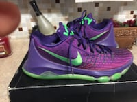pair of purple-and-green Nike Kevin Durant shoes with box