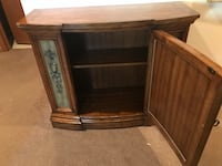 Brown wooden framed credenza cabinet with shelf storage inside. Green accent