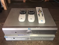 two gray DVD players with remote controls
