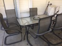 Glass table with 4 black metal framed armchairs Kelowna, V1X 1Y9