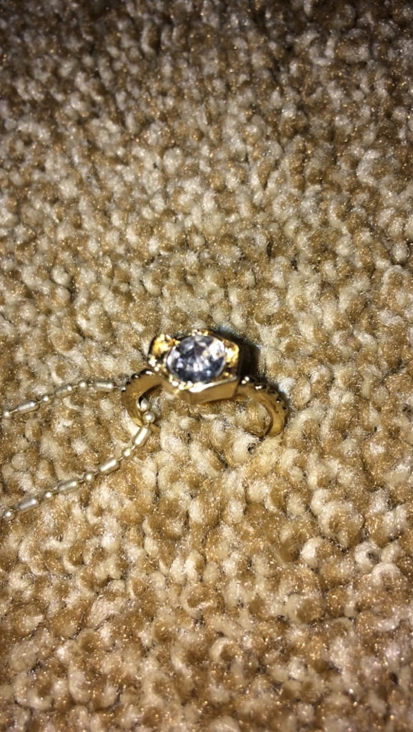gold-colored diamond encrusted solitaire ring