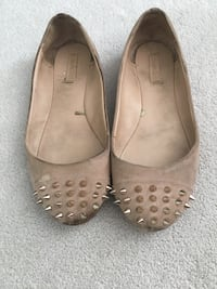Pair of beige leather nail studded slip-on shoes