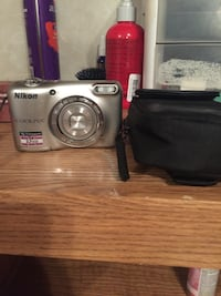 Silver Nikon Coolpix point and shoot camera with bag