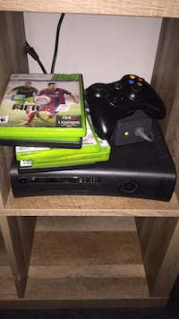 Xbox 360 console with black controller and game cases