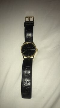 round gold analog watch with black leather strap Bristow