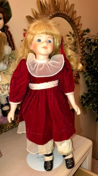 Beautiful porcelain doll with blonde hair, blue eyes, and a red dress. Comes with a doll stands, in good condition.  Coral Springs, 33065