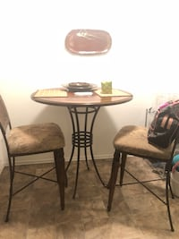 round brown wooden table with two chairs