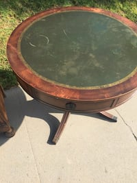 Brown and black wooden round pedestal table with leather top