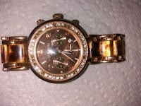 round gold chronograph watch with gold link bracelet Calgary