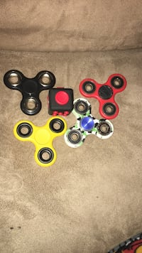 four assorted color fidget spinners and black and red fidget cube