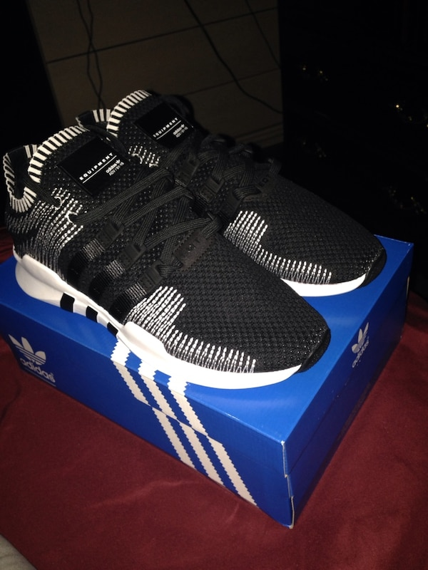pair of black Adidas EQT with box