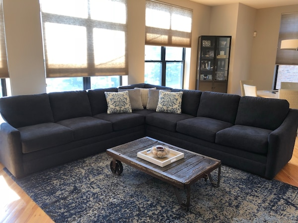 Navy blue fabric sectional sofa with throw pillows