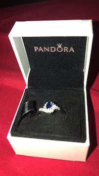 silver-colored blue gemstone encrusted Pandora engagement ring with white box