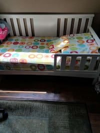 white wooden day bed frame with mattress