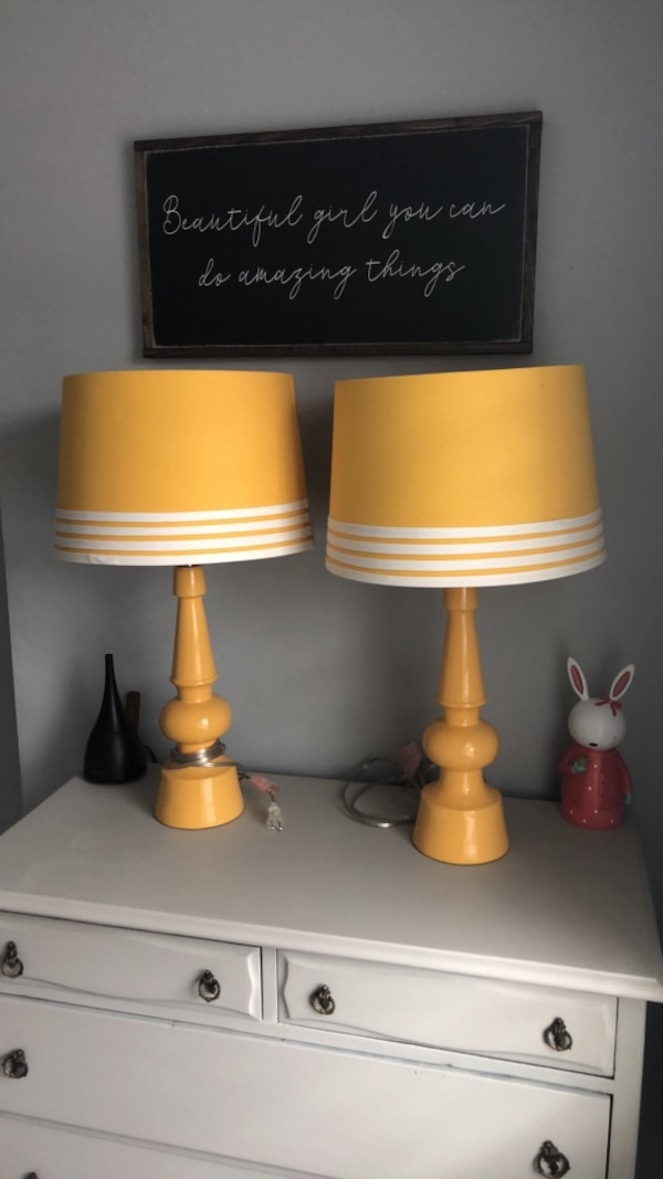 Two tall yellow table lamps.  d29f8108-46ad-4709-8e67-b3b1805a5fa4