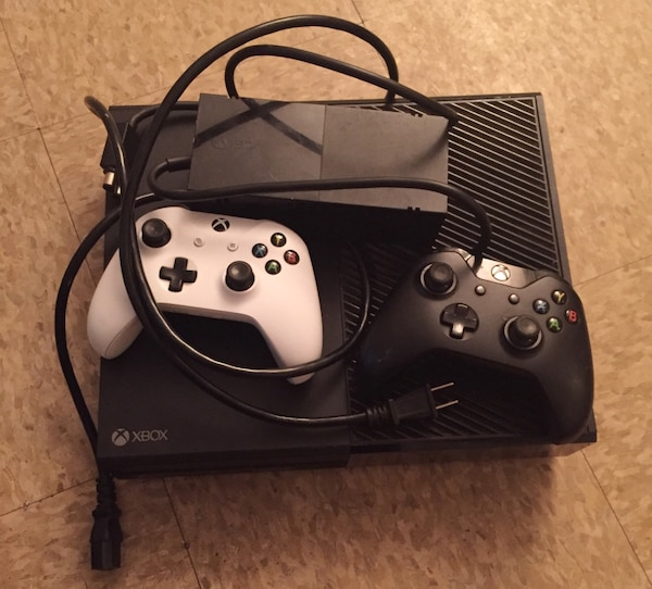 Black xbox one console with 2 controller