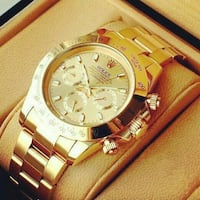 round gold-colored Rolex chronograph watch with link bracelet