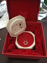 silver-colored pendant necklace with box