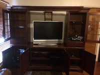 black flat screen TV with brown wooden TV hutch null