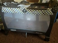 baby's white, black, and green Graco pack and play
