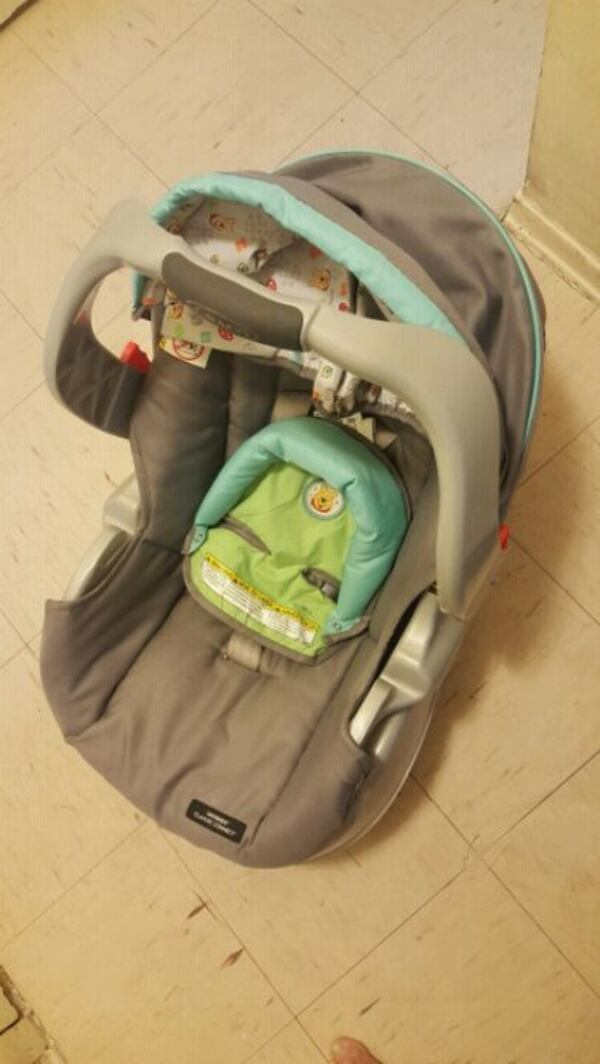 baby's gray and green car seat carrier. 88dd9285-227a-4478-abe4-152f28b05ec0