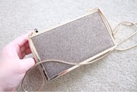 Gold-colored leather wristlet