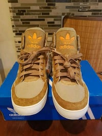 pair of brown-and-white Adidas sneakers 550 km