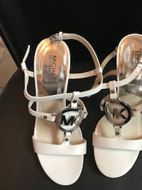 women's pair of white Micheal Kors leather open-toe pumps