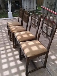 two brown wooden framed white leather padded chairs